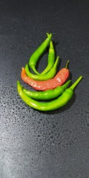 bunch of green and red chilli peppers with wet black background