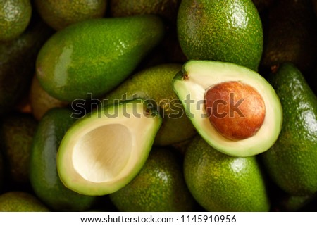Bunch of green Avocados. One of them is opened that the stone and the pulp are visible #1145910956
