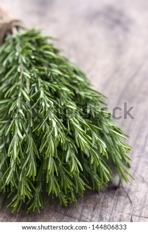 Bunch of green fresh rosemary herbs on rustic wooden table background