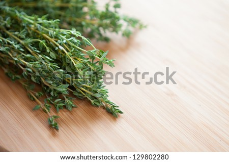 bunch of green thyme on a wooden surface, herbs closeup