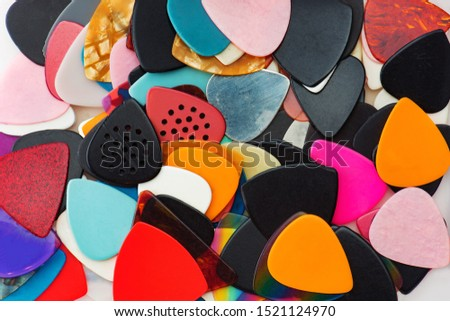Bunch of Guitar picks scattered. Guitar picks are in real life condition.