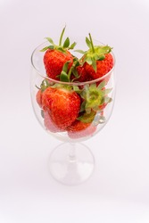 Bunch of juicy strawberries in a wine glass on a white background