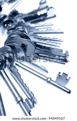 Bunch of keys on plain background - stock photo
