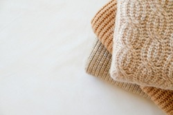 Bunch of knitted warm pastel color sweaters with different knitting patterns folded in stack, clearly visible texture. Stylish fall-winter season knitwear clothing. Close up, copy space for text.