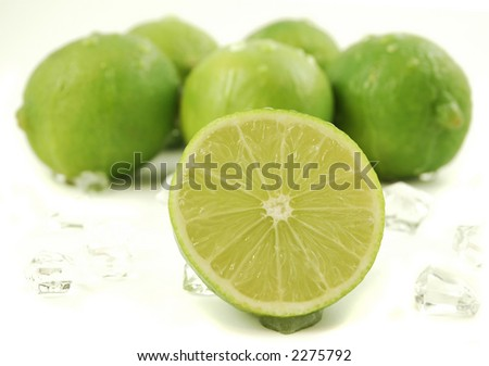 Bunch of limes surrounded by ice cubes isolated on a white background