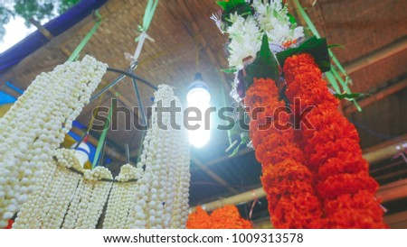 Bunch of marigold garland with white lily hanging for sale low angle shot from india.  - Shutterstock ID 1009313578