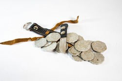 Bunch of old Indian currency coins with a small pirate knife and lathered cover on white background