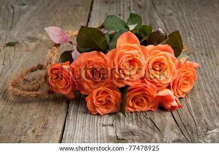 Bunch of orange roses on old wooden table