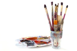 bunch of paint brushes in a glass and a used palette with colors, isolated on white background