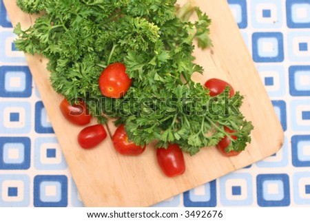 Bunch of parsley and cherry red tomatoes on wooden board and blue-squared mat.