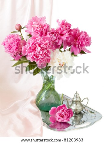 Bunch of peonies in vase on silver tray isolated on white