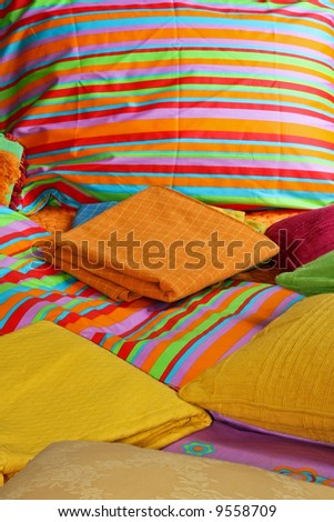 Bunch of pillows and colorful sheets over bed