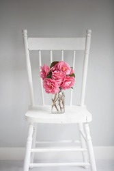 Bunch of pink camellia flowers in clear glass vase on a vintage, white chair. Vertical.