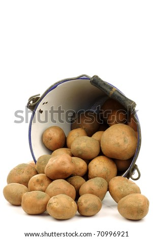 bunch of potatoes coming out of an old enamel bucket on a white background