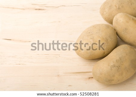 Bunch of potatoes on wood background.