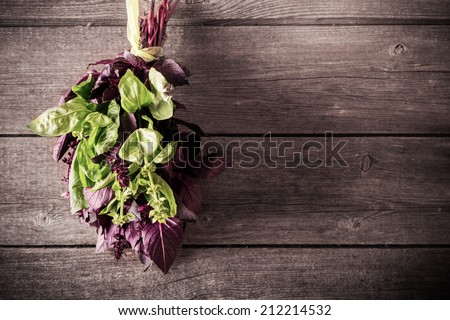 bunch of purple and green basil on a wooden background