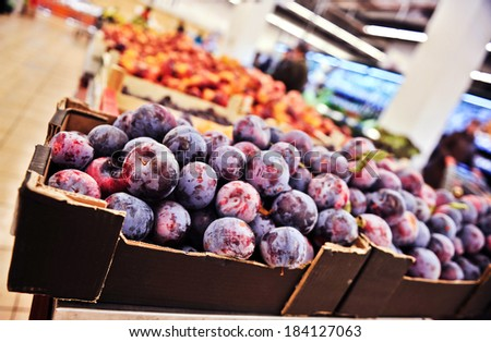 Bunch of purple plums in supermarket. Wide angle shot