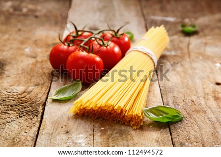 Bunch of raw spaghetti with a truss of tomatoes in a rustic scene