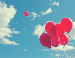 Bunch of red balloons on a blue sky with one balloon escaping to be individual and free - concept for following one's dreams