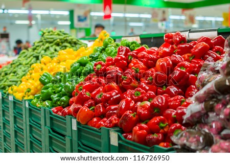 Bunch of red, green and yellow paprika pepper and radish on boxes in supermarket - stock photo