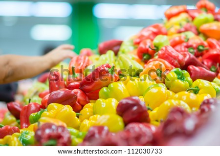 Bunch of red, green and yellow paprika peppers in supermarket. Customers selecting paprika