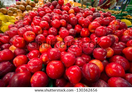 Bunch of red plums in supermarket. Wide angle shot