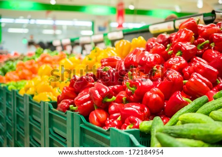 Bunch of red, yellow and orange paprika peppers on boxes in supermarket