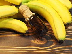 Bunch of ripe bananas and drink syrup in a bottle on a bright wooden background, closeup, flat layout. Natural healthy fruits musa for dietary nutrition