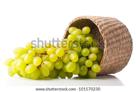 Bunch of ripe white grapes in a wicker basket on a white background