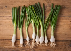 bunch of spring onions on wood
