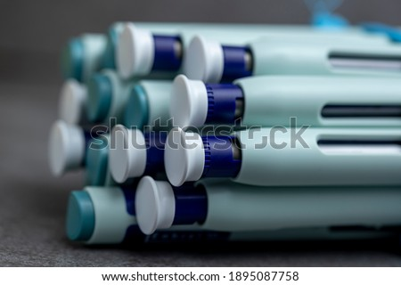 Bunch of syringe self application pens on rustic gray kitchen counter background with mix of ends and fronts. Studio medical equipment still life concept with auto-injector disposable devices.