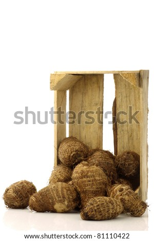 bunch of taro root (colocasia) in a wooden crate on a white background