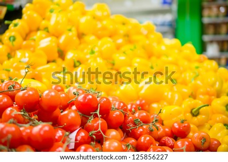 Bunch of tomatoes and paprika peppers on back in supermarket