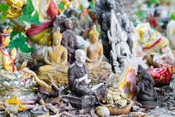 Bunch of various old and weathered small buddhist statues background. Dark brown monk statue in the front is in camera focus