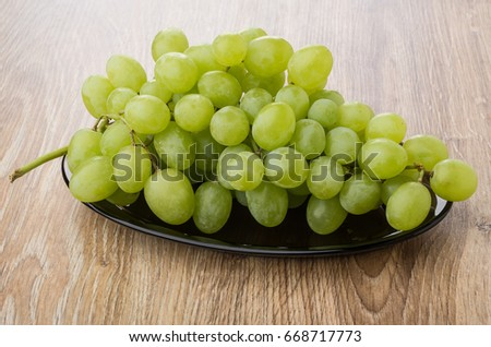 Bunch of white grapes in oval dish on wooden table #668717773