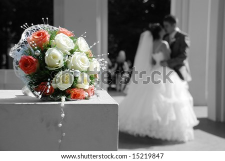 Bunch of white roses and newly-weds on a blackly white background