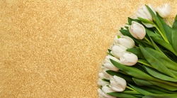 Bunch of white tulip flowers on gold background, closeup. Happy Easter card. Fresh spring flowers. Copy space for text. Wallpaper or holidays card. Mothers day, Birthday celebration concept.