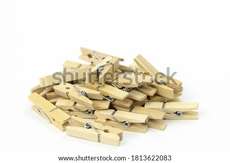 """Photo of  bunch of wooden clothespins piled up in mess on white background close up . beech wood, natural materials """"no plastic!"""" concept"""