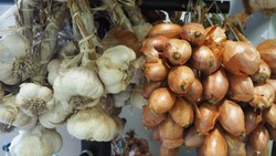Bunches of dried garlic and onions hanging on the rail for sale in food market.
