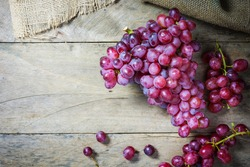 Bunches of fresh ripe red grap on a wooden textural surface. Ancient style, a beautiful background. Red wine grapes. dark grapes, blue grap, wine grap