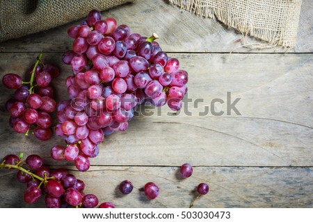 Bunches of fresh ripe red grapes on a wooden textural surface. Ancient style, a beautiful background with a branch of blue grapes. Red wine grapes. dark grapes, blue grapes, wine grapes