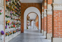 Bunches of plastic flowers in front of the small graves under a aisle with arc and a tall metal staircase with wheels