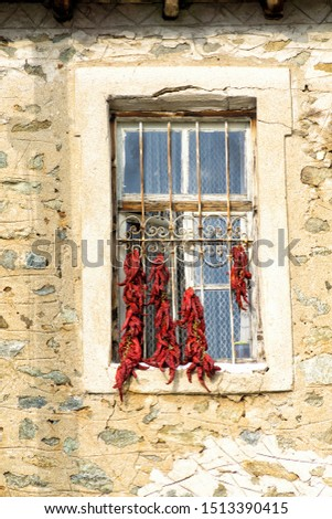 Bunches of red peppers dried in the sun hang in front of the window of old rustical building. #1513390415