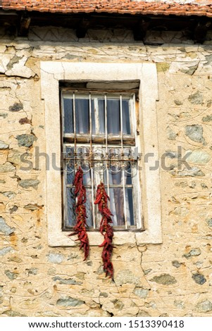 Bunches of red peppers dried in the sun hang in front of the window of old rustical building. #1513390418