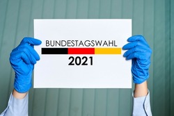 Bundestagswahl 2021 - A person in medical gloves holds a placard with the Bundestag election symbol