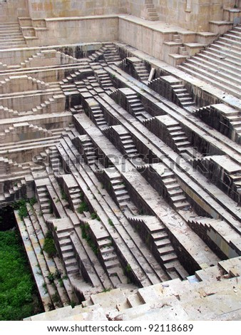 Bundi, India: amazing medieval stepwell of Dabhai Kund, built in 1658 by Chatra Sal, with its characteristic inverted-pyramid shape, and spectacular carvings on the steps leading down to water level.