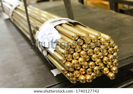 Bundle of bright shiny industrial brass rods in a market tied together with product information slip in close up on the ends Foto stock ©