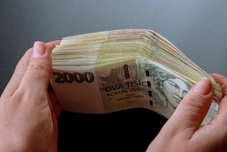 Bundle of Czech money in the hands of a woman. Banknotes of 2000. Czech crowns.