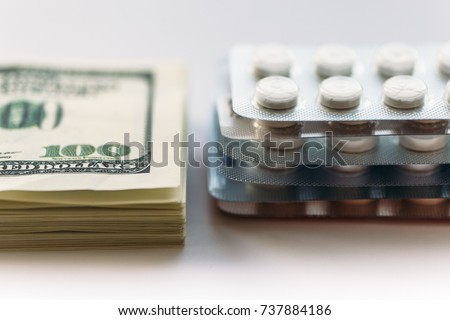 Bundle of money and  pack of medication tablets or drug pills, close-up. Expensive health care concept, selective focus
