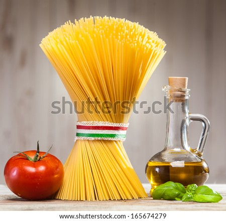 Bundle of uncooked dried Italian spaghetti tied with a ribbon in the colours of the national flag - red, white and green - on a kitchen counter with fresh basil leaves, tomato and a jar of olive oil